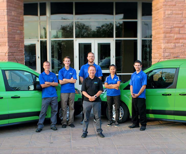 Smart Carpet Cleaning company crew in front of two green Smart Carpet Cleaning vans